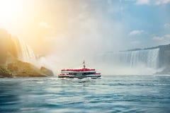 Det Niagara Falls fartyget turnerar dragningen Turist- folk som nästan seglar på loppfartyget den Niagara hästskonedgången på sol Arkivfoto
