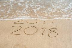 Det nya året 2018 är det kommande begreppet - inskriften 2017 och 2018 på en strandsand, vågen täcker nästan siffrorna 2017 Royaltyfria Bilder