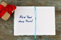 Det nya året det nya planet - smsa på notepaden med gåvan Affärsmotivati Arkivfoton