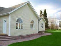 Det nya hemmet med tegelsten går och välva sig fönster Arkivfoto