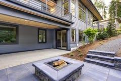 Det nya moderna hemmet presenterar en trädgård med uteplatsen arkivfoton
