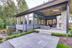 Det nya moderna hemmet presenterar en trädgård med uteplatsen royaltyfri fotografi