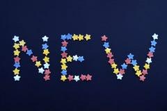 Det nya ordet är skriftligt i tunn typ av sockerbakelsestjärnor på en blå bakgrund, för som annonserar, komrets, försäljningar royaltyfria foton