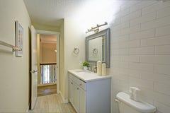 Det nytt renoverade badrummet presenterar ljus - blå badrumfåfänga royaltyfri fotografi