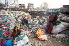 Det oidentifierade barnet sitter, medan hon föräldrar arbetar på förrådsplats Arkivfoto