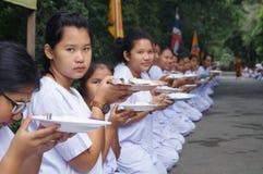 Det oidentifierade folket ger matofferings till buddistiska munkar Royaltyfri Bild