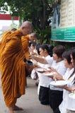 Det oidentifierade folket ger matofferings till buddistiska munkar Royaltyfria Foton