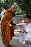 Det oidentifierade folket ger matofferings till buddistiska munkar Royaltyfri Fotografi