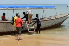 Det oidentifierade lokala folket hjälper turisterna att klättra på boaen royaltyfri fotografi
