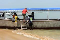 Det oidentifierade lokala folket hjälper turisterna att klättra på boaen arkivbild