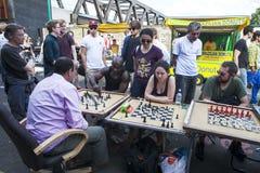 Det oidentifierade lokala folket spelade schack på tegelstengrändgatan Arkivbilder