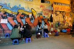 Det oidentifierade ungdomfolket äter på gatamatförsäljare i Hanoi gamla fjärdedel på natten Royaltyfri Fotografi