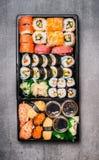 Det olika sushivalet i svart förpackande magasin på grå färger stenar bakgrund, bästa sikt arkivbild