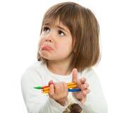 Olycklig liten flicka med crayons. Arkivbild