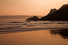 Det orange glödet av solnedgången reflekterade i de våta sanderna av den Threecliff fjärden, Goweren Royaltyfri Foto
