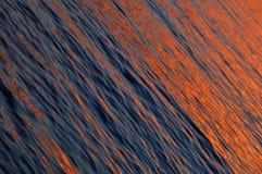 Det orange havet vinkar på havssolnedgången Arkivfoton