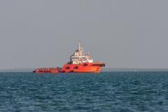 Det orange räddningsaktionskeppet seglar över fjärden på solnedgången Arkivbild