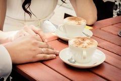 Det ovanliga älska bröllopparet i kafé dricker cappuccino Arkivfoto