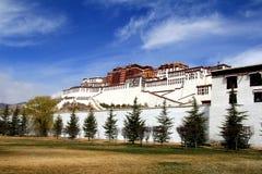 Det panorama- av den Potala slotten, med den inre Folkrepubliken Kina flaggan såväl som Potala slottfyrkant, träd och meado Royaltyfria Foton