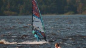 Det panorama- skottet av mannen i blåa baddräktritter vindsurfar i sjön på höjdhastighet stock video