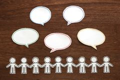 Det pappers- folket med färgrikt tomt dialoganförande bubblar på brunt trä svart telefon för kommunikationsbegreppsmottagare arkivbilder