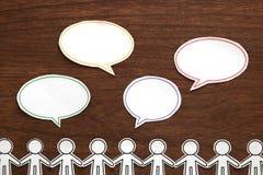Det pappers- folket med färgrikt tomt dialoganförande bubblar på brunt trä svart telefon för kommunikationsbegreppsmottagare royaltyfri bild