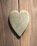 Det pappers- hålet rev sönder i hjärta Shape med gammal Wood bakgrund inom Royaltyfri Foto