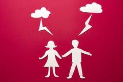 Det pappers- origamifolket man och kvinnainnehavhänder under åskmoln med blixt Fara- och attackbegrepp bryter skyen royaltyfri bild