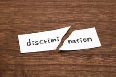 Det pappers- skriftligt som diskriminering är sönderrivet på trä Begrepp av avskaffande av diskriminering royaltyfri foto