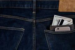 Det pengar-, debiteringkortet och kreditkorten är i fack av blå jean på träbakgrund med kopieringsutrymme Arkivfoton