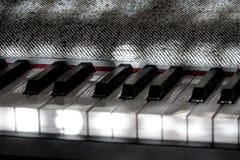 Det perfekta pianot stämmer i milt solljus med grå färgräkningen Royaltyfri Fotografi