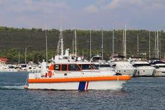 Det pilot- fartyget seglar vattnet av marina bland förtöjde segla yachter Hjälp, i att förtöja skytteln i hamnstaden kust royaltyfri bild