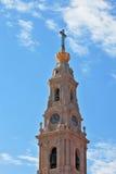 Det pittoreska tornet som överträffas av ett kors arkivbild
