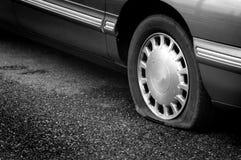 Det plana gummihjulet på farligt strandsatt för vägfara deflaterar deflaterat Royaltyfri Foto