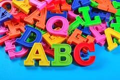 Det plast- färgade alfabetet märker abc:et på en blått Arkivfoton