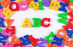 Det plast- färgade alfabetet märker abc:et på en vit Arkivfoto
