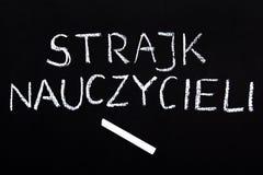 Det polska ordet LÄRARE SLÅR på en svart tavla royaltyfri foto