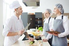 Det positiva barnet internerar kockar som frågar kocken på mästarklass royaltyfria foton