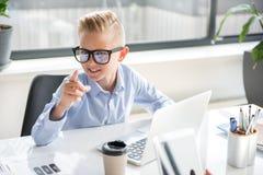 Det positiva gulliga barnet arbetar på bärbara datorn royaltyfri bild