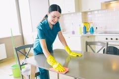 Det positiva kvinnliga rengöringsmedlet ser ner och lutar för att bordlägga Hon gör det ren Flickan arbetar i studiolägenhet i kö royaltyfria bilder