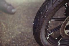 Det punkterade motorcykelhjulet, en spika klibbar ut ur gummihjulet, gummihjulmontering royaltyfria bilder