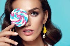 Det purpurfärgade sminket och färgrikt ljust spikar Kvinnlig modell With Candy för mode arkivfoto