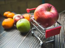 Det röda äpplet är på Mini Shopping Cart royaltyfri foto