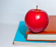 det röda äpplet ligger på läroböcker Arkivfoto