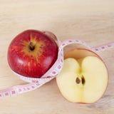 Det röda äpplet med cm på den wood tabellen för bantar begrepp royaltyfri fotografi