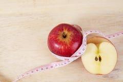 Det röda äpplet med cm på den wood tabellen för bantar begrepp arkivfoto