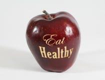 Det röda äpplet med orden - äta sunt Royaltyfri Fotografi