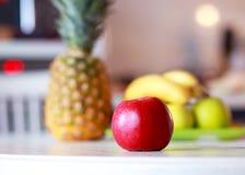 det röda äpplet och exotiska frukter är på tabellen arkivbilder