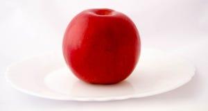 Det röda äpplet på en vit pläterar Arkivbilder