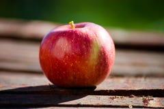 Det röda äpplet på trä bordlägger Arkivfoton